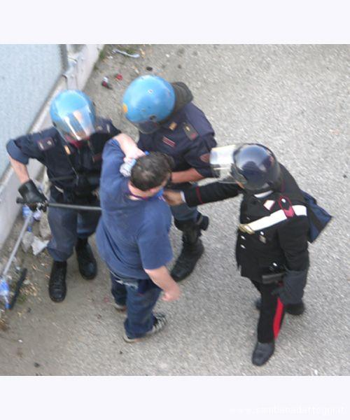 Tre agenti si avvicinano all'imputato, che si tiene una bottiglietta d'acqua sulla nuca