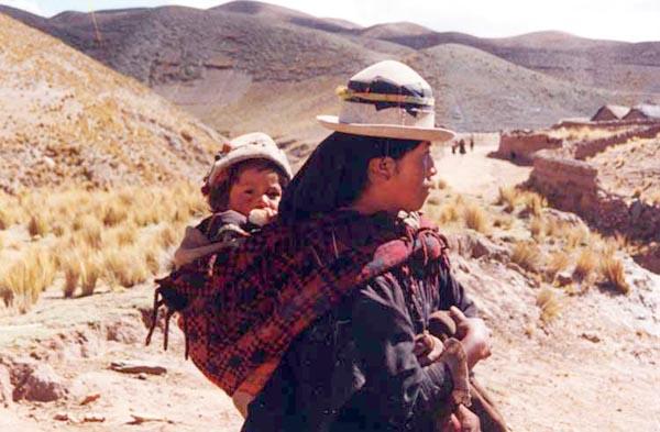 Una mamma peruviana porta in spalla il suo bambino