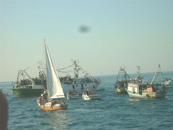Barche e motopescherecci in corteo dietro al motopeschereccio con l'icona della