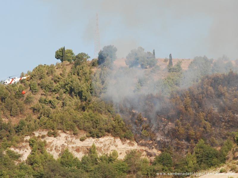 L'incendio divampato stamattina, 18 agosto, a Ripatransone. A sinistra l'elicottero dei pompieri, visibile anche l'antenna