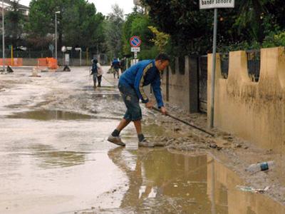 Un cittadino intento a spalare il fango