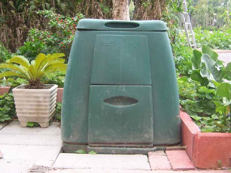 Una compostiera: i rifiuti organici vengono inseriti dal coperchio superiore e il compost prodotto viene prelevato dallo sportello inferiore