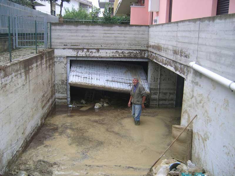 Un tortoretano mentre svuota un garage ancora parzialmente allagato. Il livello dell'acqua domenica scorsa era salito fino al piano terra