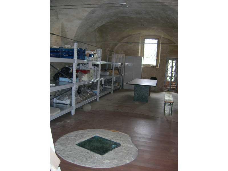 Il laboratorio del museo, dove sono custoditi i reperti di Colle di Marzio. In primo piano la cisterna seicentesca della casa doganale, sulla quale è stata eseguita una parziale copertura protettiva in legno
