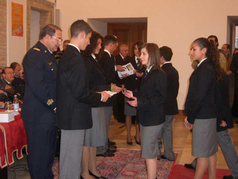 Gli studento mentre ricevono il distintivo e una copia della Costituzione