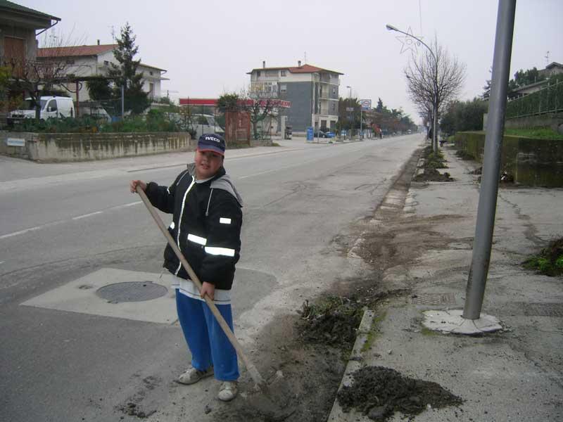 Anche un ragazzino partecipa all'iniziativa di pulizia delle strade