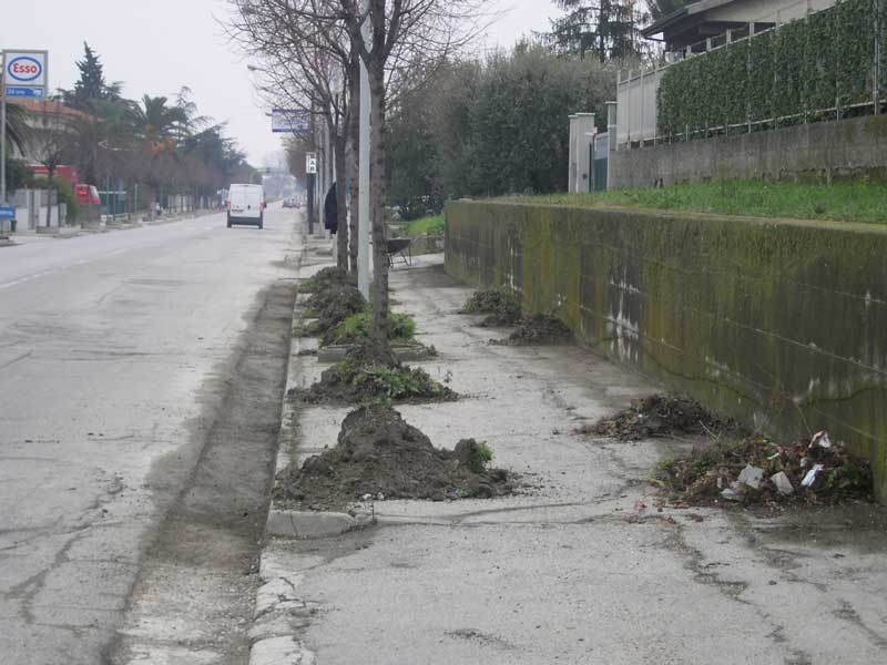 Un marciapiede durante i lavori di pulitura da fango e rifiuti