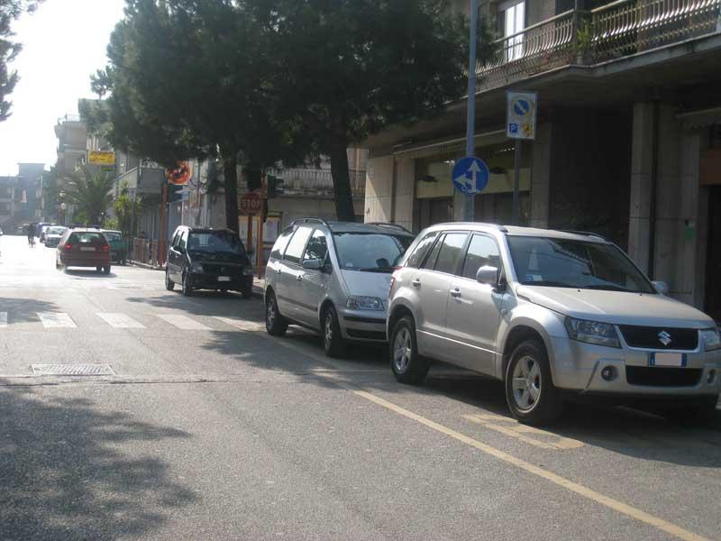 Via Cesare Battisti, davanti alla scuola media: parcheggio nell'area destinata al bus, sulla zona destinata ai disabili e proprio a ridosso dell'incrocio con via D'Annunzio