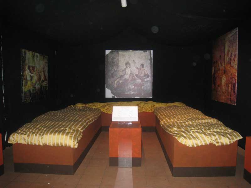 Riproduzione di un triclinium: durante i pranzi ufficiali i commensali si disponevano sdraiati sul triclinium e prelevavano i cibi da un tavolo centrale