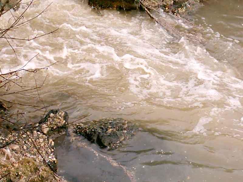 Uno scarico convoglia i liquami nelle acque del fiume