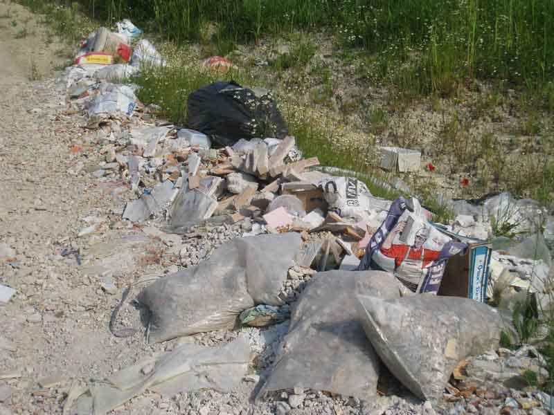 Sacchi di rifiuti vari abbandonati da tempo lungo una strada del quartiere residenziale di Vallecupa