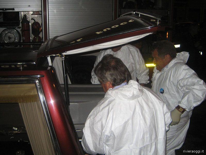La bara con il cadavere da poco estratto dall'auto in fiamme davanti all'ospedale