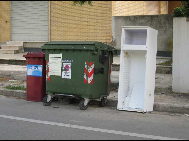 bidoni e rifiuti ingombranti disposti su un tratto di carreggiata destinato a parcheggio