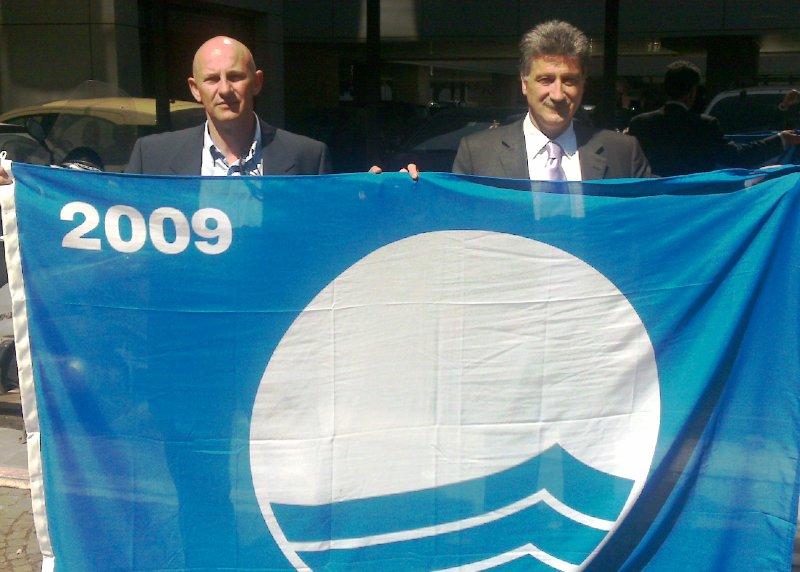 L'assessore all'ambiente Giuseppe Marconi e il Sindaco Luigi Merli con la bandiera blu 2009