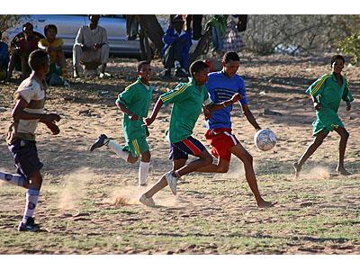 Partita di calcio tra San. I più abbienti possono permettersi un paio di scarpe, gli altri giocano scalzi