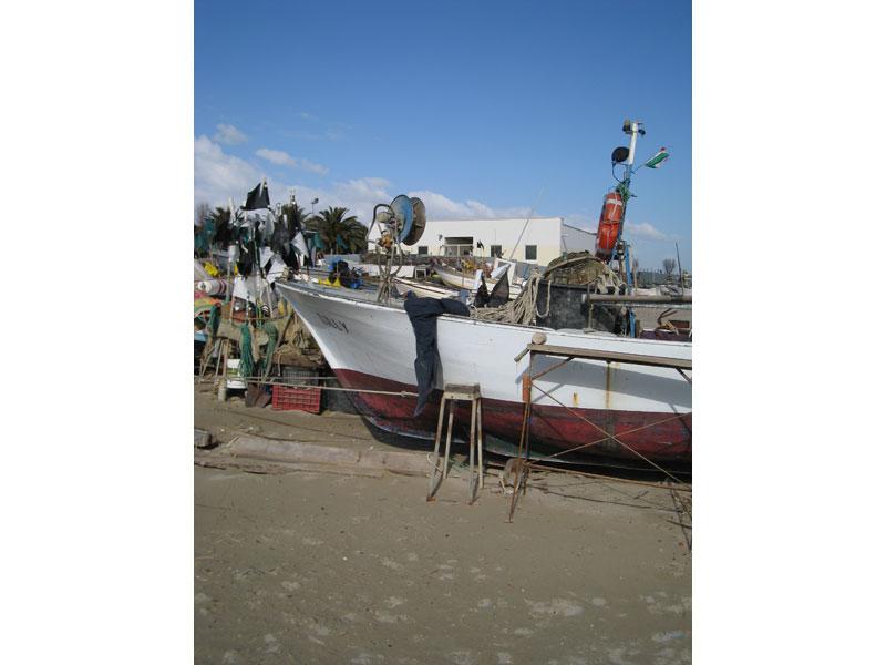 Una barca sulla spiaggia di Martinsicuro. Sullo sfondo il Centro polifunzionale per la piccola pesca