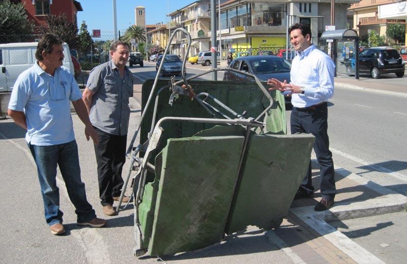 Il consigliere comunale Fernando Gabrielli, a sinistra, con il sindaco Stracci, a destra, discutono nel punto dove è avvenuto l'incidente di domenica 19 settembre, come testimonia il cassonetto distrutto dall'impatto. Con loro Vittorio Malizia