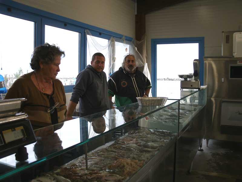 I pescatori all'interno di un box per la vendita del pesce, sul lungomare grottammarese