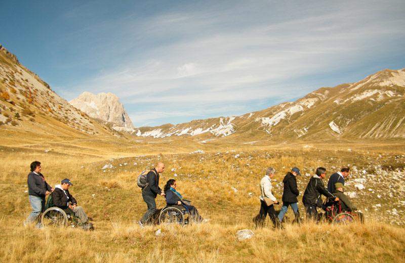 Persone in carrozzina percorrono i sentieri di montagna nella giornata