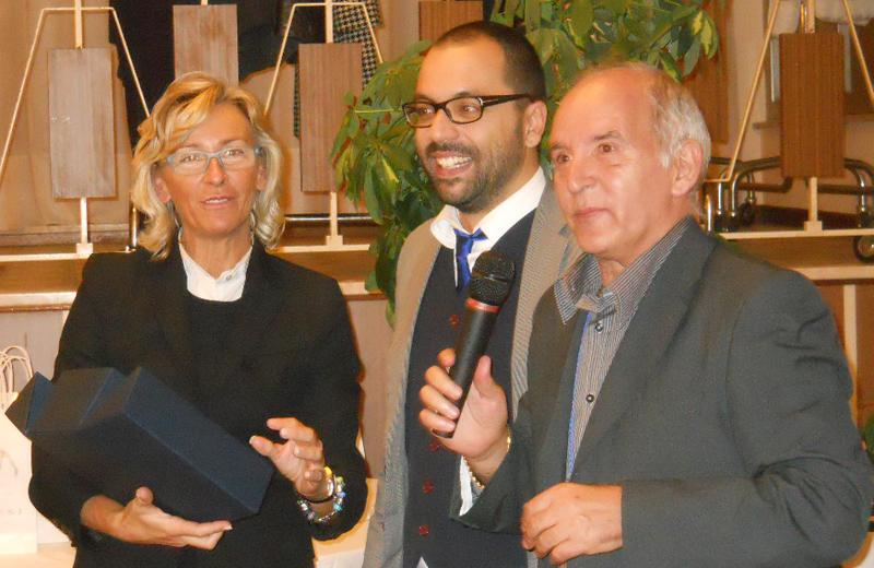 L'assessore alla Cultura Sorge e Mimmo Minuto premiano l'editor Rizzoli Michele Rossi (al centro)