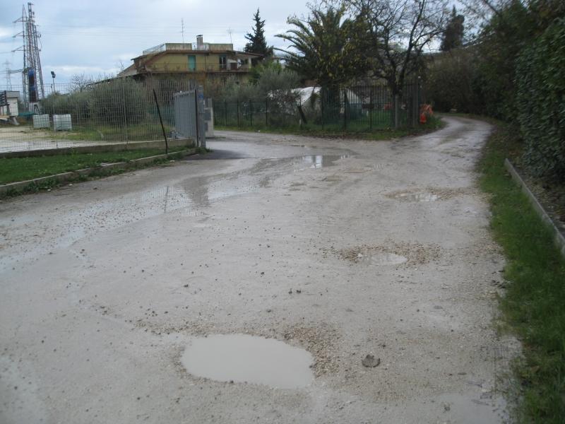 La strada piena di buche dinanzi alla casa di Mario Calvaresi