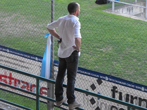 Il tecnico del Grottammare Giuseppe De Amicis aggrappato alla rete di recinzione della tribuna del  Pirani durante la gara contro la Fermana