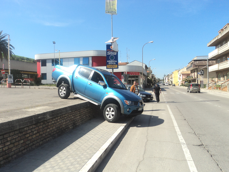 L'auto sospesa tra il parcheggio e la statale 16