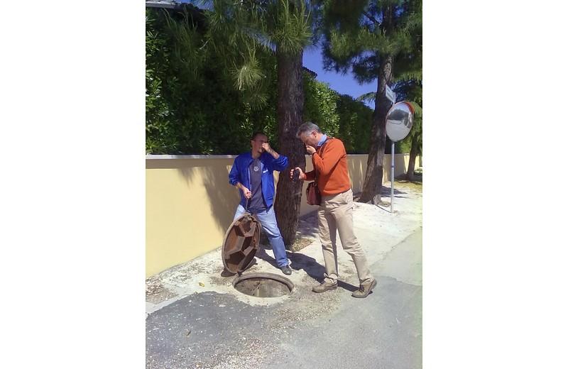 Andrea mattioli e Giovanni Marucci del Movimento Cinque Stelle mostrano i tombini dai quali fuoriescono gli odori nauseanti legati al vicino giacimento di metano, in contrada Montecretaccio