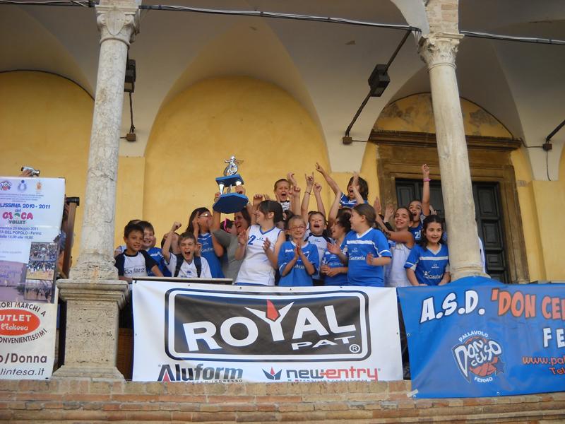 Anna Pulcini, l'allenatrice di minivolley della Gagliarda, alza al cielo il trofeo del GiocaVolley coi suoi bambini festanti