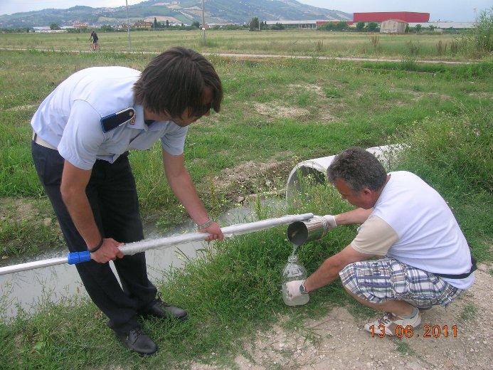 Un vigile urbano insieme al consigliere comunale dei Verdi Andrea Marinucci durante il prelievo di un campione d'acqua del torrente