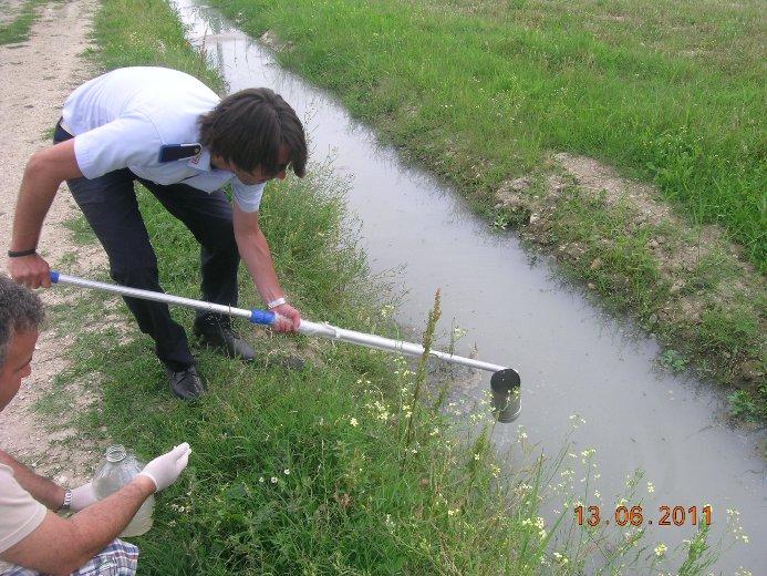 Un vigile urbano durante il prelievo di un campione d'acqua del torrente