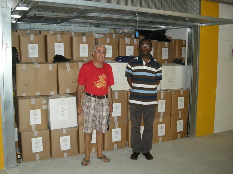 Fortunato Amabili e il dottor Gerard Ngome Enang davanti a del materiale da consegnare in beneficenza all'interno di un garage prestato da amici