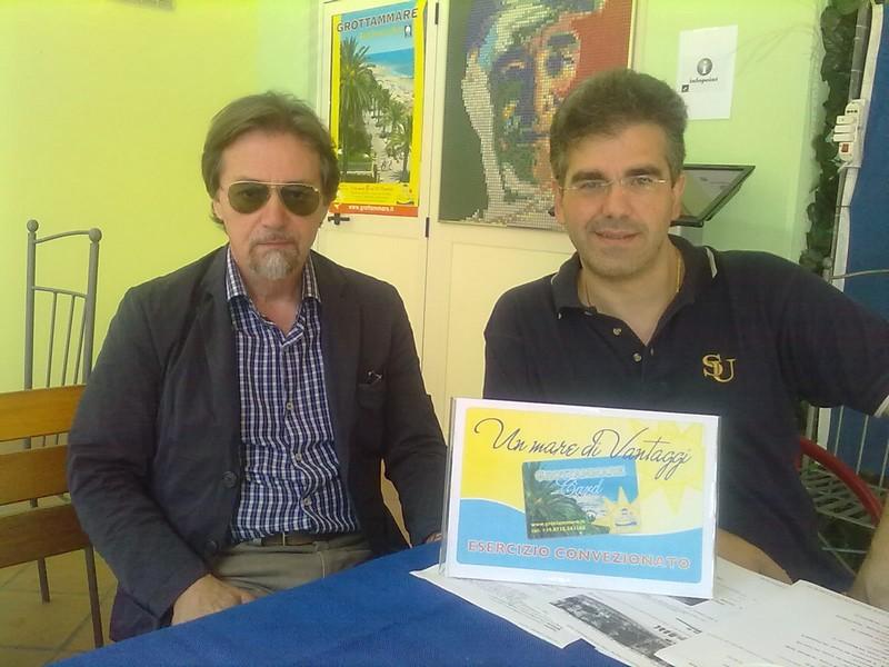 Ugo Grossetti e Umberto Scartozzi, vicepresidente e presidente dell'associazione operatori turistici di Grottammare, con la vetrofania della Grottammare Card