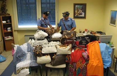 Carabinieri con parte della merce sequestrata nell'operazione di contrasto al commercio abusivo