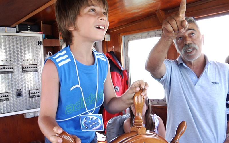 Un bambino governa il timone nella gita in barca Blu Card