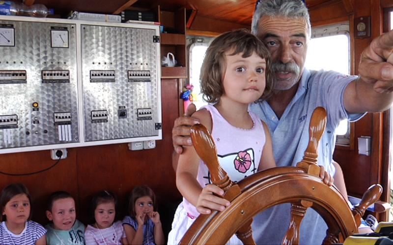 Una bambina governa il timone nella gita in barca della Blu Card