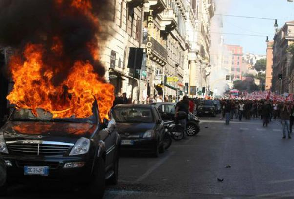 Roma in mano ai black bloc, auto in fiamme in via Cavour
