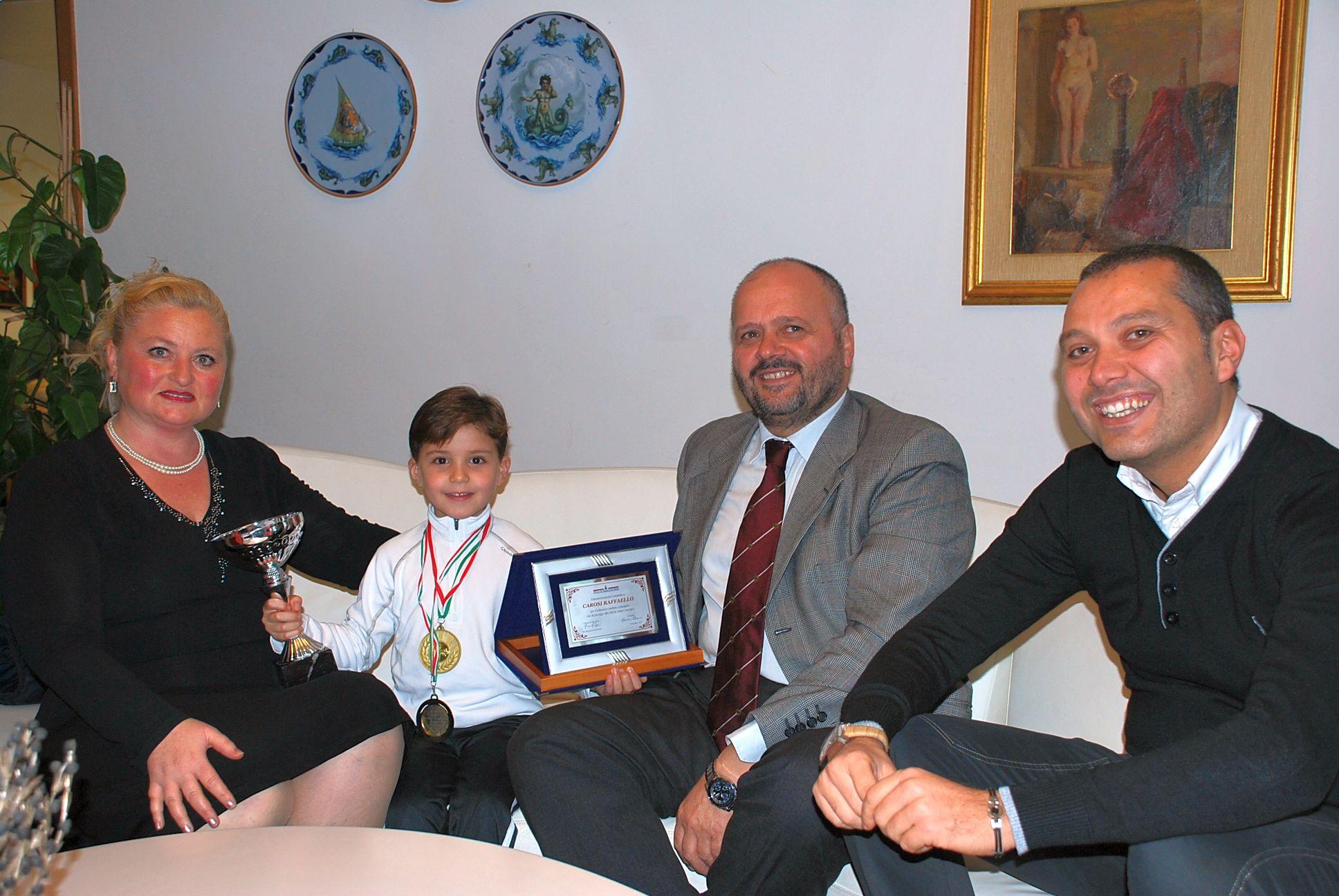 Raffaello Carosi con la mamma premiato da Gaspari e Curzi