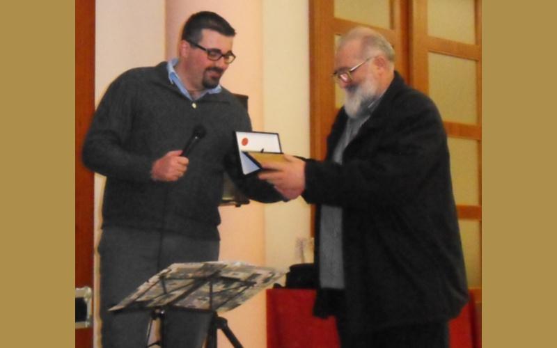 Simone Incicco consegna la targa a Don Anselmo