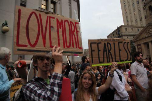 Una manifestazione di Occupy Wall Street e un cartello esplicito, ama di più e abbi meno paura