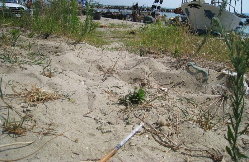 una siringa tra la sabbia