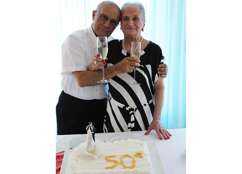 Gli sposi brindano davanti alla classica torta... cinquantenaria