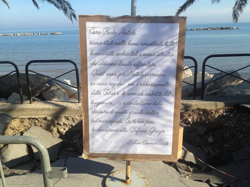 Il cartello posto dai commercianti del lungomare nei pressi dell'enorme buca