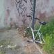 Bicicletta abbandonata tra la sporcizia e l'erba alta