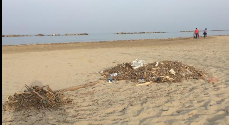 Detriti in spiaggia prima della pulizia