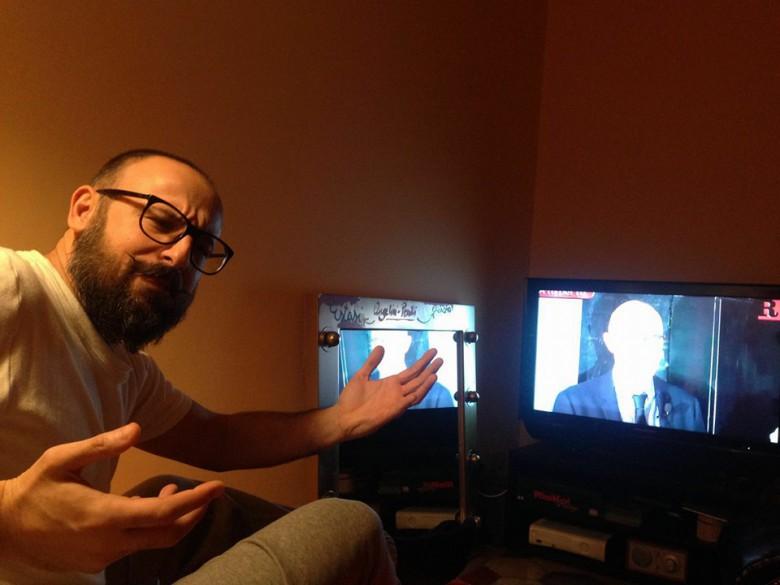 Luigi Maria Perotti guarda A tu per tu con Riviera Oggi e Margherita Sorge dallo schermo tv