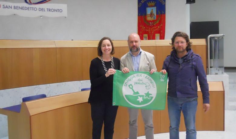 """La bandiera verde con cui sabato 16 aprile saranno premiate le 134 città vincitrici nel 2016. A sinistra Anna Marinangeli (Direttore dell'Ufficio Turismo e Cultura di San Benedetto), al centro Andrea Perugini (Associazione Albergatori """"Riviera delle Palme"""")"""