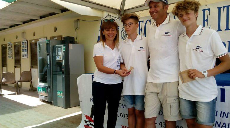 Il presidente Adele Mattioli regala un portafortuna ai due giovani regatanti. Al centro l'allenatore Romolo Emiliani